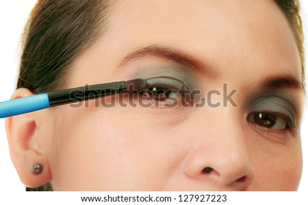 Isolated middle age woman with a make up brush - stock photo