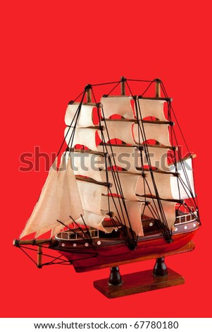 isolated model of luxury sailboat on red background - stock photo