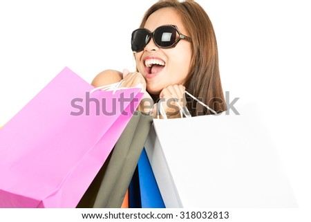 Isolated on white close up headshot portrait ecstatic Asian female shopper wearing fashionable sunglasses holding colorful department store shopping bags while showing playful and joyful attitude - stock photo