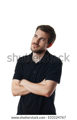 Isolated on white image of a young man deep in thought, as he stands arms folded looking off into the distance - stock photo