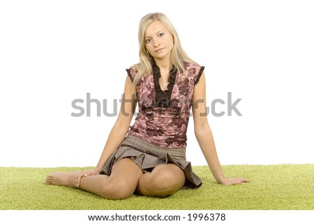 isolated on white young blonde woman sitting on the green carpet - stock photo