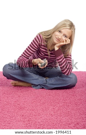 isolated on white young blonde woman sitting on the pink carpet with remote control - stock photo