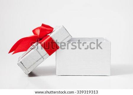 Isolated open gift box with red ribbon and bow on white background - stock photo