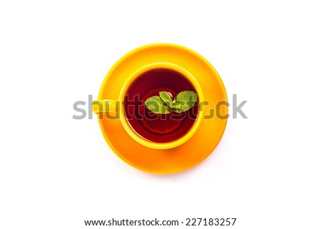 Isolated orange cup and saucer with lemon and mint leaf top view on a white background. - stock photo