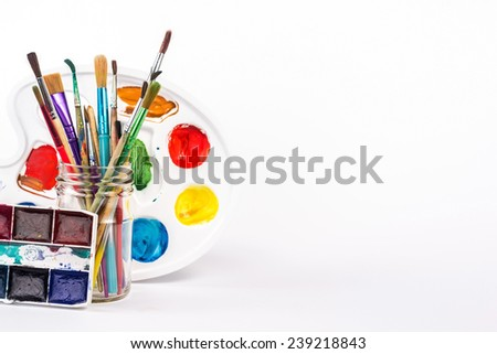 isolated paints palette and paints brushes in glass - stock photo