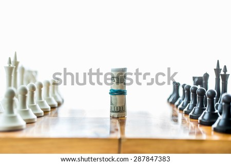Isolated photo of twisted money on board between rows of chess pieces - stock photo