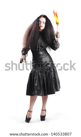 Isolated picture of a woman in elgant black dress with jester makeup holding a flaming torch. - stock photo