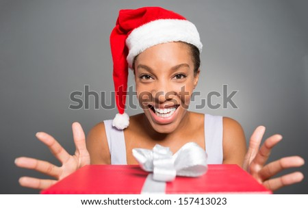 Isolated portrait of a cheerful young woman taking a x-mas present on the foreground - stock photo