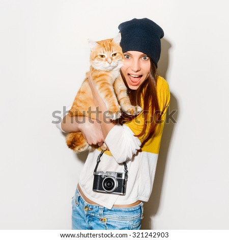 Isolated portrait of a happy crazy hipster girl with camera  and ginger cat  in a yellow baize and jeans on white background. Retro camera. Hipster girl - stock photo