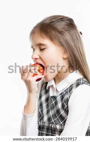 Isolated portrait of cute schoolgirl biting fresh red apple - stock photo