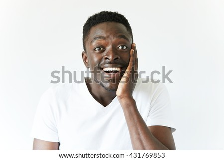 Isolated portrait of shocked young attractive African American male looking in full disbelief, hand on cheek, surprised with some unexpected news. Positive human emotions and facial expressions - stock photo