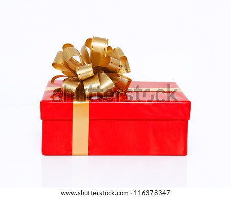 Isolated red gift box with a gold bow on New Year holiday - stock photo