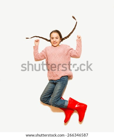Isolated shot from top of happy jumping girl in red rubber boots - stock photo
