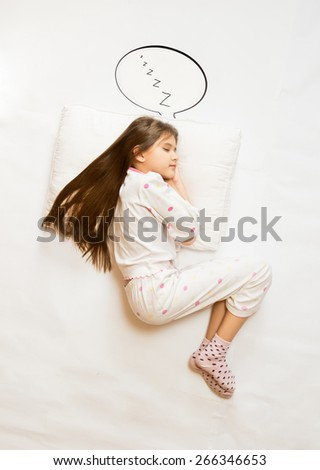 Isolated shot from top view of cute girl sleeping on big cushion with speech bubble - stock photo