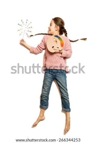 Isolated shot of cute girl holding palette and paintbrush like magic wand  - stock photo