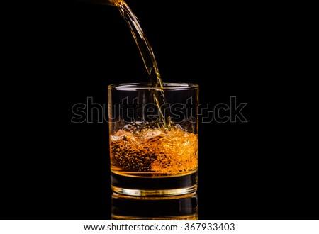 Isolated shot of whiskey with splash on black background - stock photo