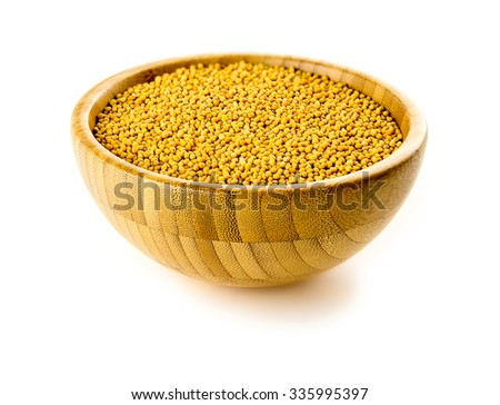 Isolated shot of yellow mustard seeds spice in traditional bowl against white background. - stock photo