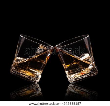 Isolated shots of whiskey glasses on black background - stock photo