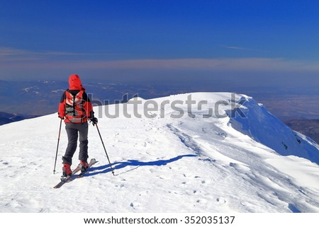 Isolated skier ascending on touring skis a snow covered summit - stock photo