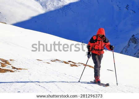 Isolated sky mountaineer traverses a white plateau on the mountain in sunny winter day - stock photo