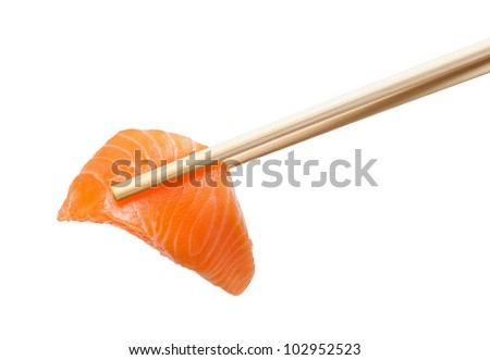 Isolated sliced raw salmon with chopsticks holding it - stock photo