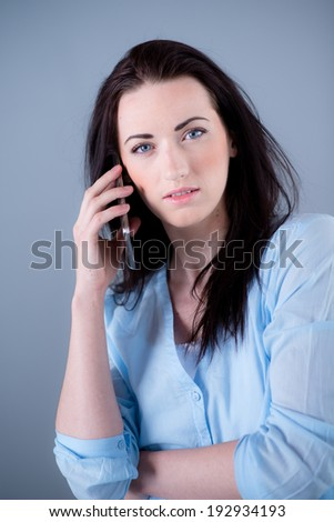 Isolated studio portrait of cheerful young woman on blue background - stock photo