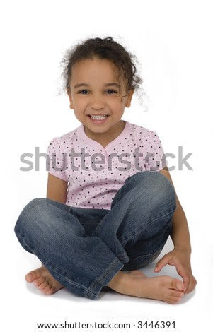 Isolated studio shot of a beautiful mixed race little girl sitting cross legged and laughing, created with a drop shadow. - stock photo