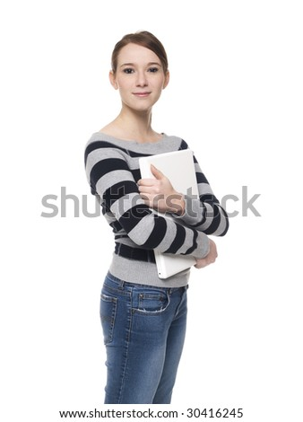 Isolated studio shot of a casually dressed young adult woman holding a laptop computer to her chest and lookign at the camera. - stock photo
