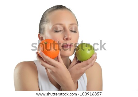 Isolated studio shot of a caucasian woman holding apples to oranges - stock photo