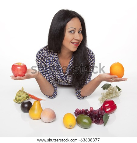 Isolated studio shot of a Latina woman weighing the options of an apple and an orange, with a variety of fruits and vegetables, deciding what to eat for her healthy diet. - stock photo