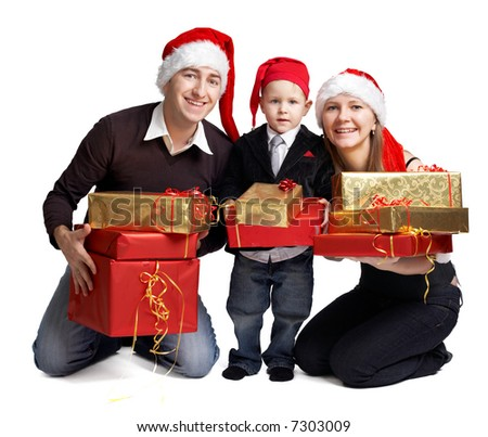 Isolated studio shot of happy young family of three wearing smart casual clothes and Santa's hats with a lot of Christmas presents. - stock photo