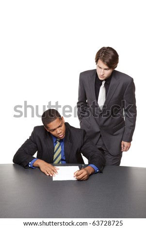 Isolated studio shot of two businessmen writing notes on a notepad at a conference table. - stock photo