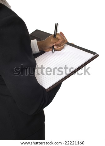 Isolated studio shot over the shoulder of a businesswoman writing on a notepad. - stock photo