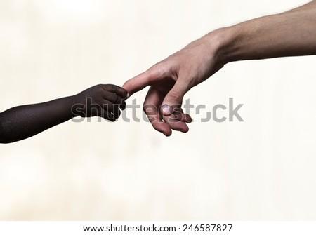Isolated: Symbols of Hope - White Man Black Child Hands - stock photo
