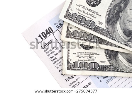 Isolated 1040 tax form with one hundred dollar bills. - stock photo