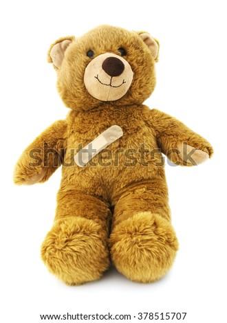 Isolated teddy bear with band aid. - stock photo