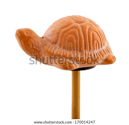 Isolated tortoise in clay on wooden stick - stock photo