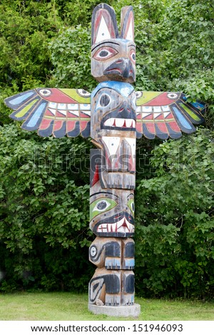 Isolated totem wood pole in the green forest background - stock photo