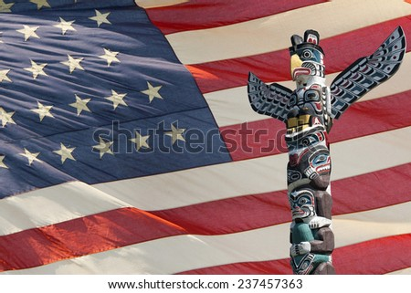 isolated totem wood pole on america star and stripes flag background - stock photo