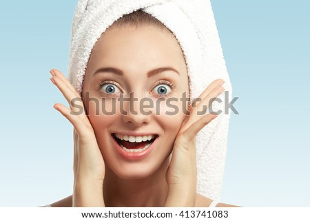 Isolated view of happy young female with white bath towel on her head having spa procedure in beauty salon. Cropped shot of excited blonde girl with healthy skin looking in surprise at the camera   - stock photo