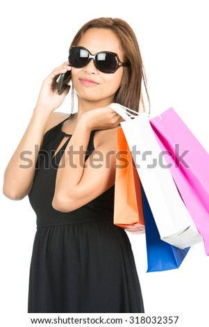 Isolated white background of a beautiful, hip, fashionable Asian shopper wearing an elegant black dress and sunglasses while talking on a mobile phone holding department store bags - stock photo