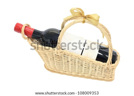 Isolated wine bottle with blank label on present basket with golden ribbon - stock photo