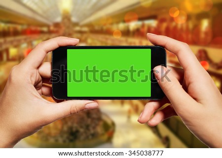 isolated woman hand holding the smart phone with isolated green screen against Christmas or New Year shopping centre background with copy space.  - stock photo