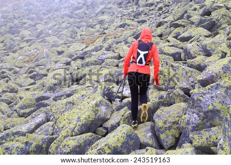 Isolated woman hiker walking on large boulders covered by fog - stock photo