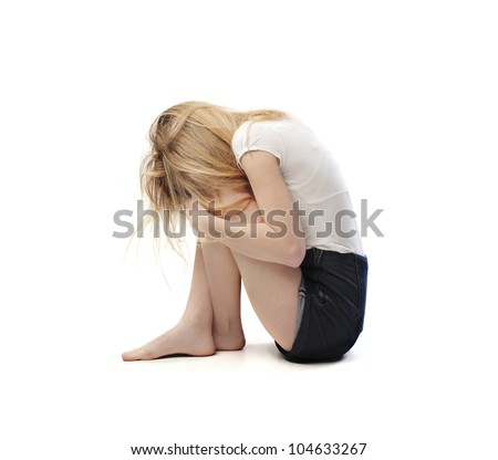 Isolated young woman hiding her head between her legs - stock photo