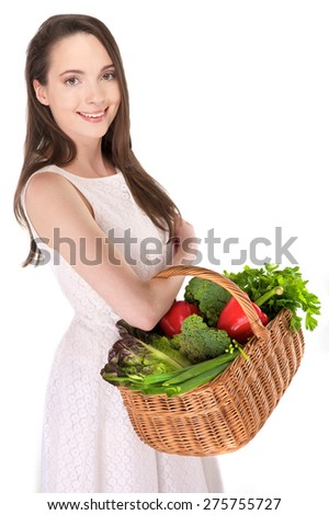 Isolated young woman holding basket of vegetables on white background - stock photo