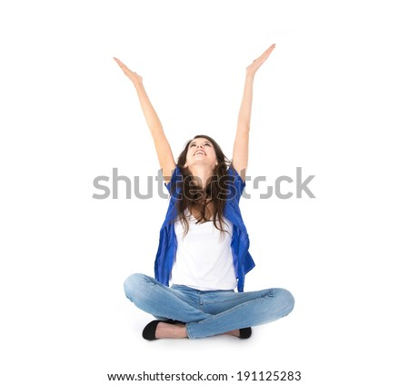 Isolated young woman with hands up sitting in crossed legs on the floor  - stock photo