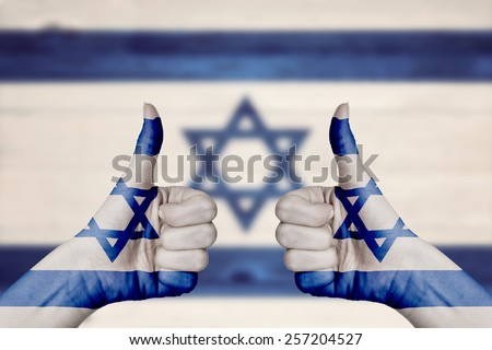 Israel flag painted on female hands thumbs up with blurry wooden background - stock photo