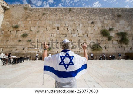 ISRAEL, JERUSALEM - OCTOBER 07, 2014: A man with an Israelian flag and his arms raised in front of the western wall in the old city of Jerusalem - stock photo