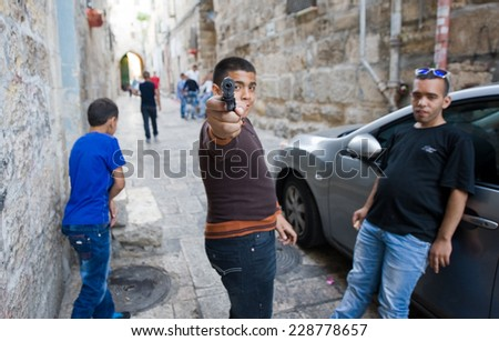 ISRAEL, JERUSALEM - OCTOBER 06, 2014: Three young muslim teenagers are playing 'war games' on the streets in the muslim quarter in the old city of Jerusalem - stock photo